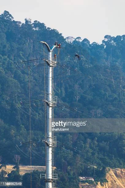 workers working on power pole at sub urban area of kuala lumpur, malaysia. - shaifulzamri 個照片及圖片檔