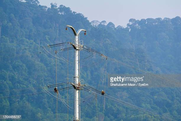 workers working on power pole at sub urban area of kuala lumpur, malaysia. - shaifulzamri stock pictures, royalty-free photos & images