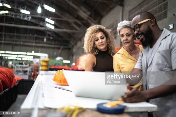 werknemers die samenwerken met laptop in de fabriek - selective focus stockfoto's en -beelden