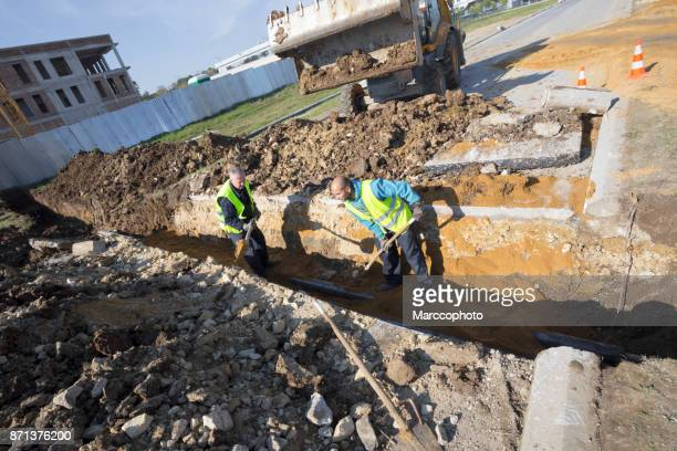 Workers works with shovel in a trench on pipeline construction site