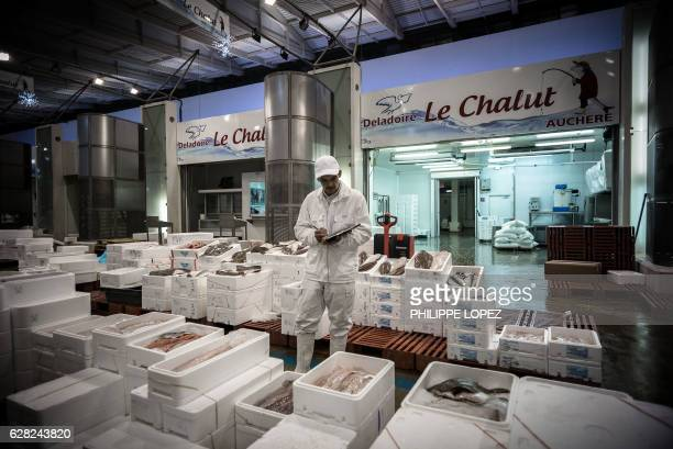 A workers writes an invoice at the fish and seafood pavilion of the Rungis international food market in Rungis a southern suburb of Paris on December...