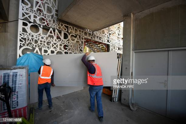 Workes carry a large board during a visit to show the newly built roof of the Philippe Chatrier central tennis court at the Roland Garros stadium in...