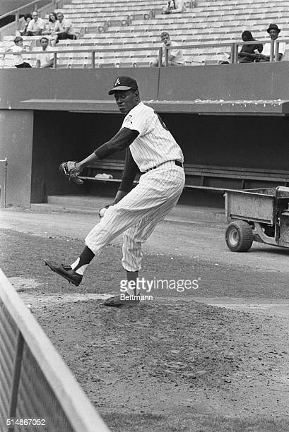 Working as a pitching coach for the Atlanta Braves, veteran pitcher Satchel Paige pitches in the bullpen. Paige played in the Negro Leagues for many...