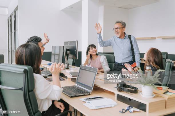 working asian chinese senior colleague greeting on each other in office morning - day 1 stock pictures, royalty-free photos & images