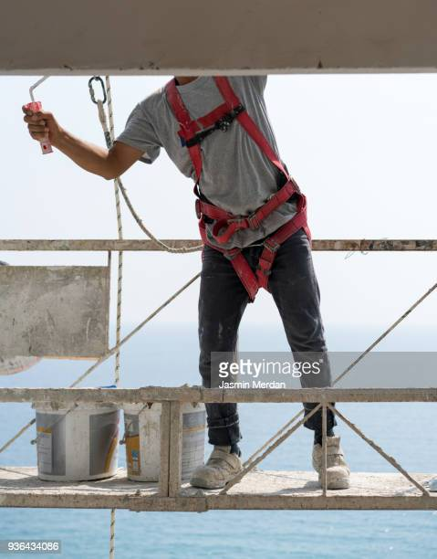 working at a high construction site - safety harness stock photos and pictures
