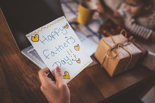 Working at home father holding father's day card and gift 983431494