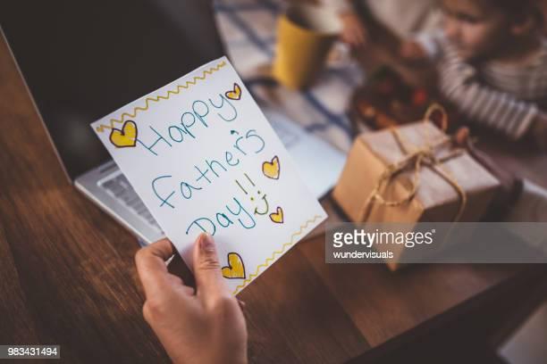 working at home father holding father's day card and gift - fathers day stock pictures, royalty-free photos & images