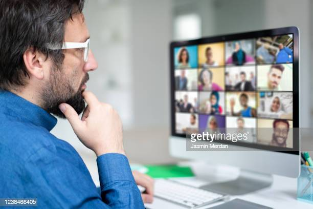 working at home having a video conference with colleagues - video still stock pictures, royalty-free photos & images