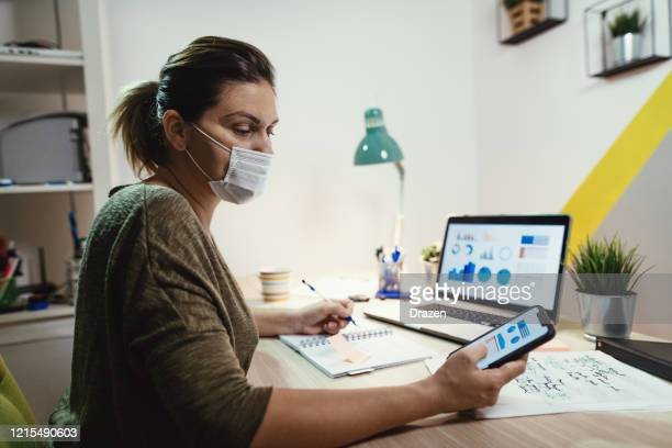working at home with face mask - pandemic illness stock pictures, royalty-free photos & images