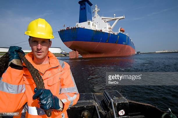 working at the harbor between big cargo ships. - dock worker stock photos and pictures