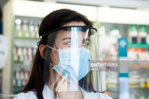 保護フェイスマスクを着用して薬局で働く - フェイスシールド ストックフォトと画像