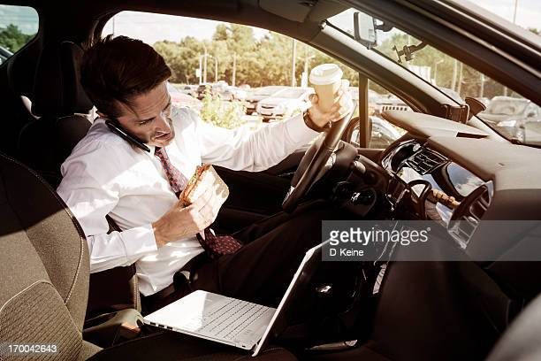 Working businessman eating inside car