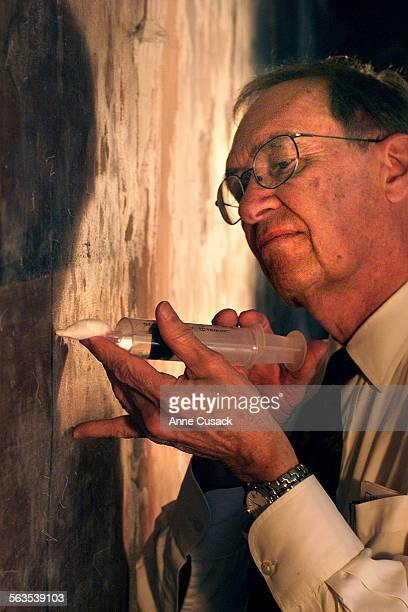 Working curator Perry Huston uses a syringe to inject poly vinyl acetate emulsion into hollow spaces behind the mural entitled Portrait of Mexico...
