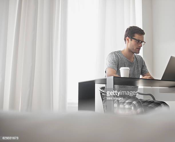 A working day. A man seated at a laptop computer, working in a hotel bedroom with a cup of coffee.