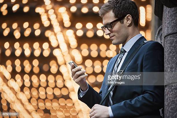 A working day. Businessman in a work suit and tie on a city street, checking his phone.