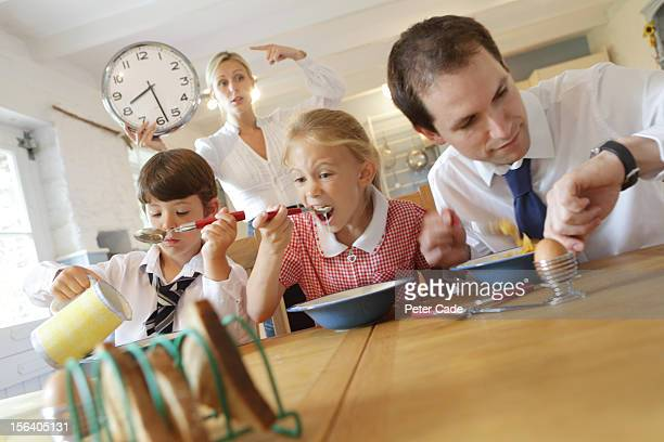 working family at breakfast, mum pointing at clock - urgency stock pictures, royalty-free photos & images
