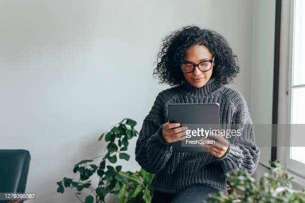 working from home: a young woman using a digital tablet to read/watch something - see stock pictures, royalty-free photos & images