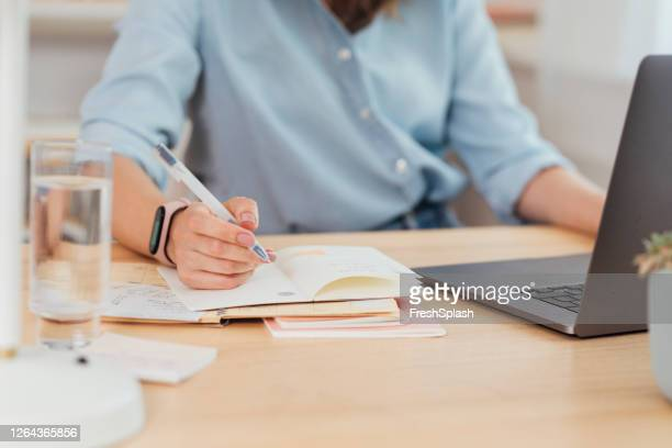 working from home: hand of a businesswoman writing notes - agenda stock pictures, royalty-free photos & images