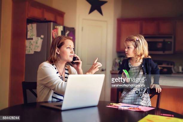 working from home mom gesturing to daughter to wait
