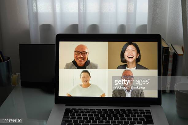 working from home with a smiling colleague on online laptop screen - テレビ会議 ストックフォトと画像