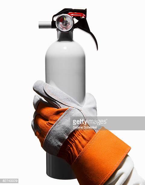 working glove holding white fire extinguish