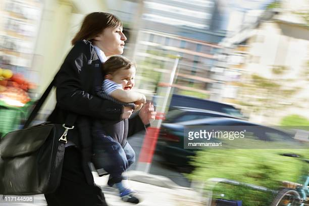 working in a rush, mom carrying infant son outdoors - dringendheid stockfoto's en -beelden