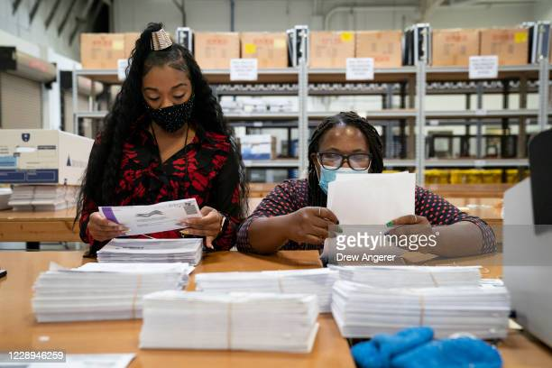 Working in bipartisan pairs, canvassers process mail-in ballots in a warehouse at the Anne Arundel County Board of Elections headquarters on October...