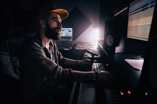 DJ working in music studio and looking at computer screen 994303656
