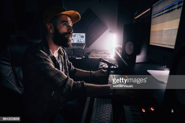 dj working in music studio and looking at computer screen - post-production stock pictures, royalty-free photos & images