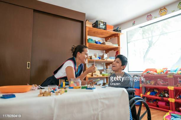 working in nursery with children with learning difficulties - boy in wheelchair with celebral palsy - weakness stock pictures, royalty-free photos & images