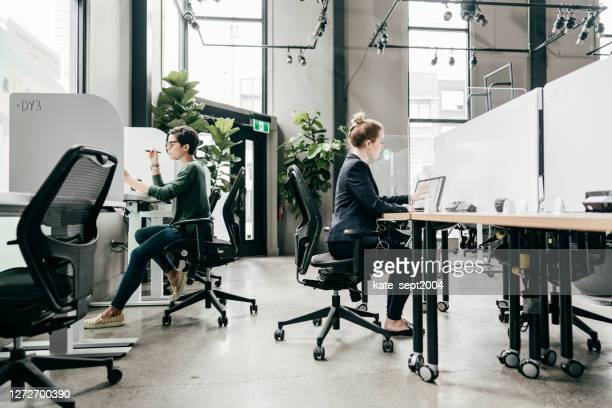 working in the office on a new project. wide angle shot of the office and people in it - business finance and industry stock pictures, royalty-free photos & images