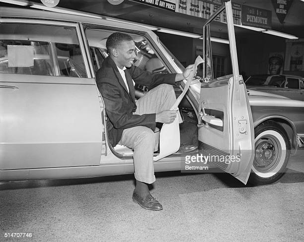 Working in the off-season as a car salesman, Chicago Cubs' star shortstop Ernie Banks sits in a car in the showroom reading a press release...