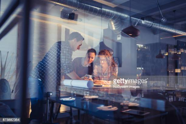 working late. group of young architects working late in office - design studio stock pictures, royalty-free photos & images