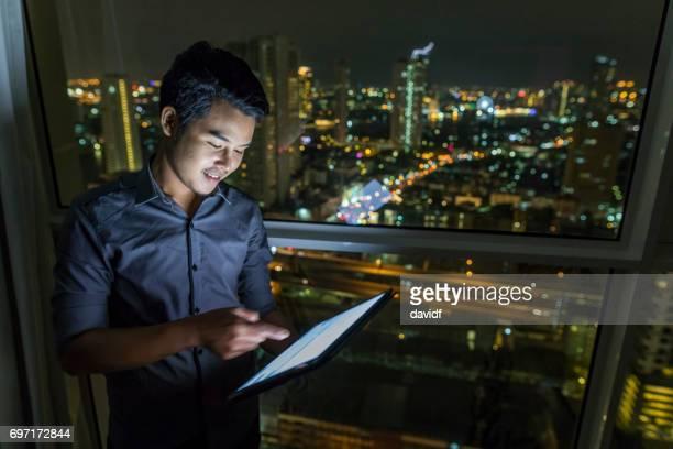 Überstunden in einem Hochhaus mit Tablet-Computer