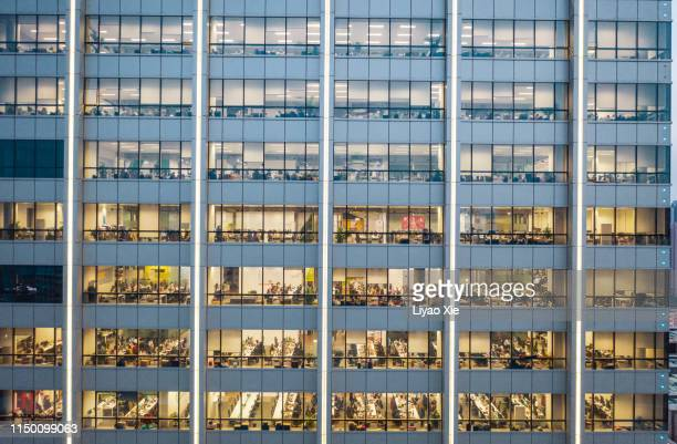 working late in the office - office block exterior stock pictures, royalty-free photos & images