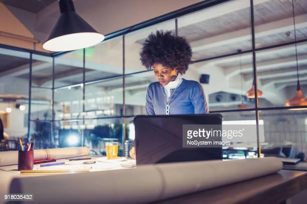 trabalhando até tarde. mulher jovem afro-americana, arquiteto, trabalhando até tarde no escritório - electric lamp - fotografias e filmes do acervo