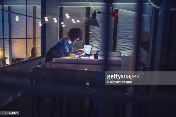 working late. young african-american woman working in office - overworked stock pictures, royalty-free photos & images