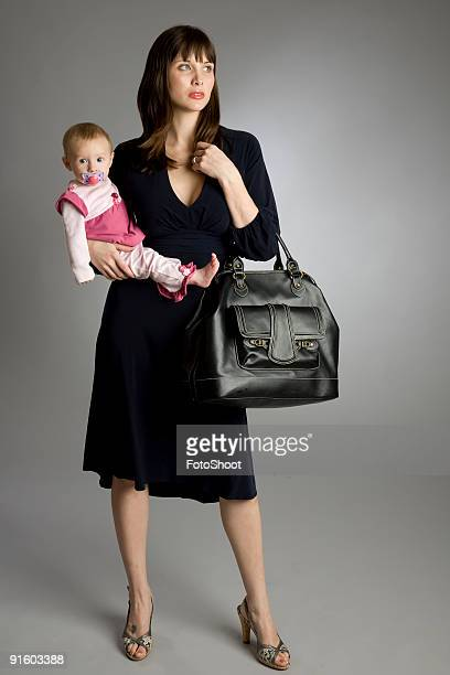A working mom dressed in business attire holding her baby