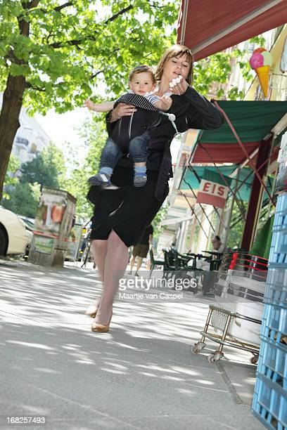 Working mom outside carrying child while looking at watch