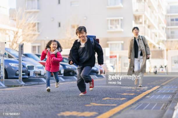 車に歩く働く母親と姉妹 - シングルマザー ストックフォトと画像