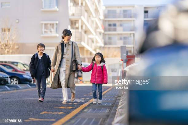 working mother and sisters walking to car - land vehicle stock pictures, royalty-free photos & images