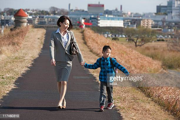 Working mother and son walking together
