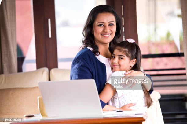 working mother embracing her daughter at home - working mother stock pictures, royalty-free photos & images