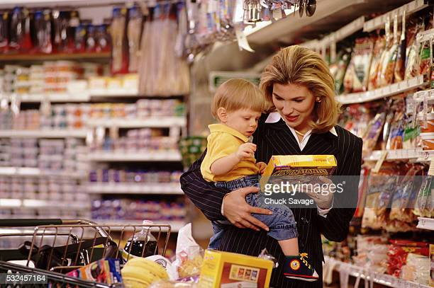 Working mother food shopping with baby