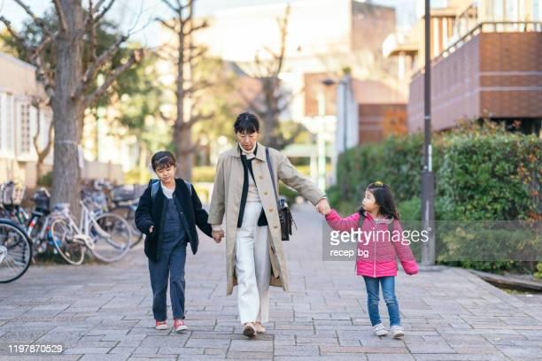 娘たちと一緒に通りを歩く働く母親 - シングルマザー ストックフォトと画像