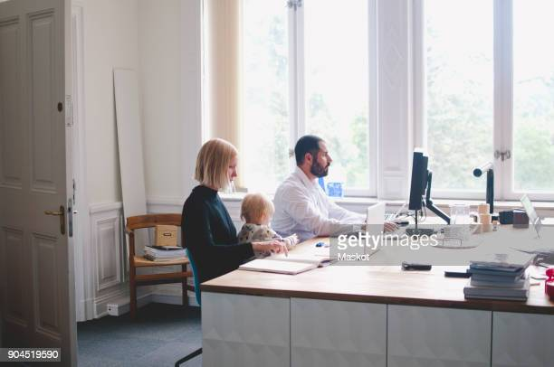 Working mother with daughter sitting by male colleague in office