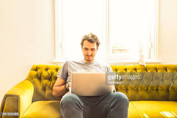 Working on a sofa with a laptop on his lap