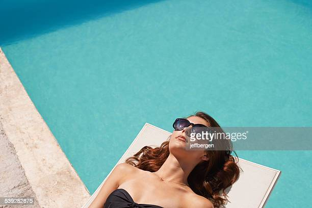 working on her tan - poolside stock pictures, royalty-free photos & images