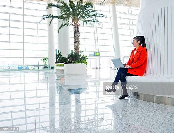 Travaillant sur un ordinateur portable dans la salle d'attente de l'aéroport