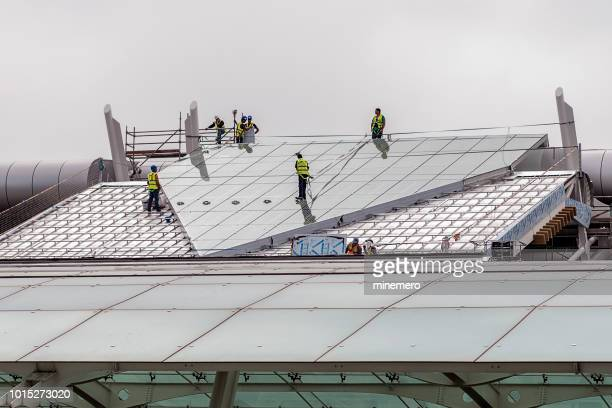 working on the industrial building roof - high up stock pictures, royalty-free photos & images
